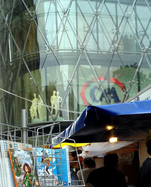 Budapest, Vörösmarty tér, 89. Ünnepi Könyvhét, 2018. június 10, C&A áruház kivilágított próbababái állnak az épület ablakában, alattuk könyves stand.