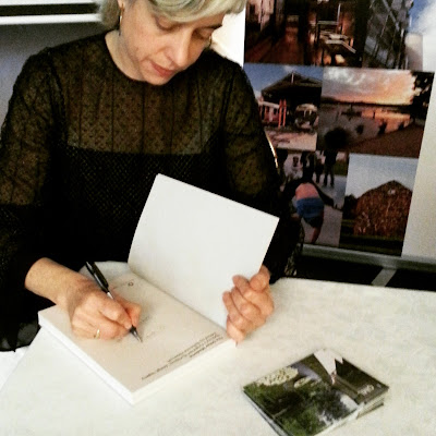 Rebecca Hawcroft signs a copy of her book The Other Moderns.
