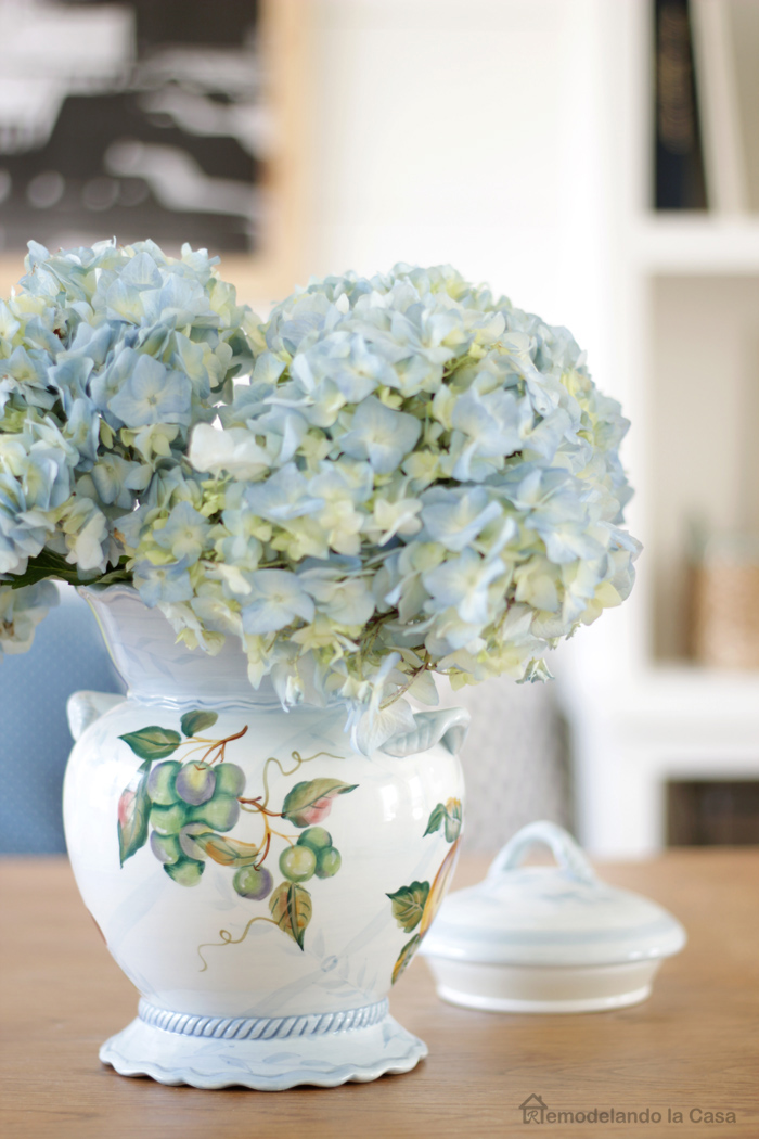 Hydrangea bouquet in blue painted vase on top of farmhouse table