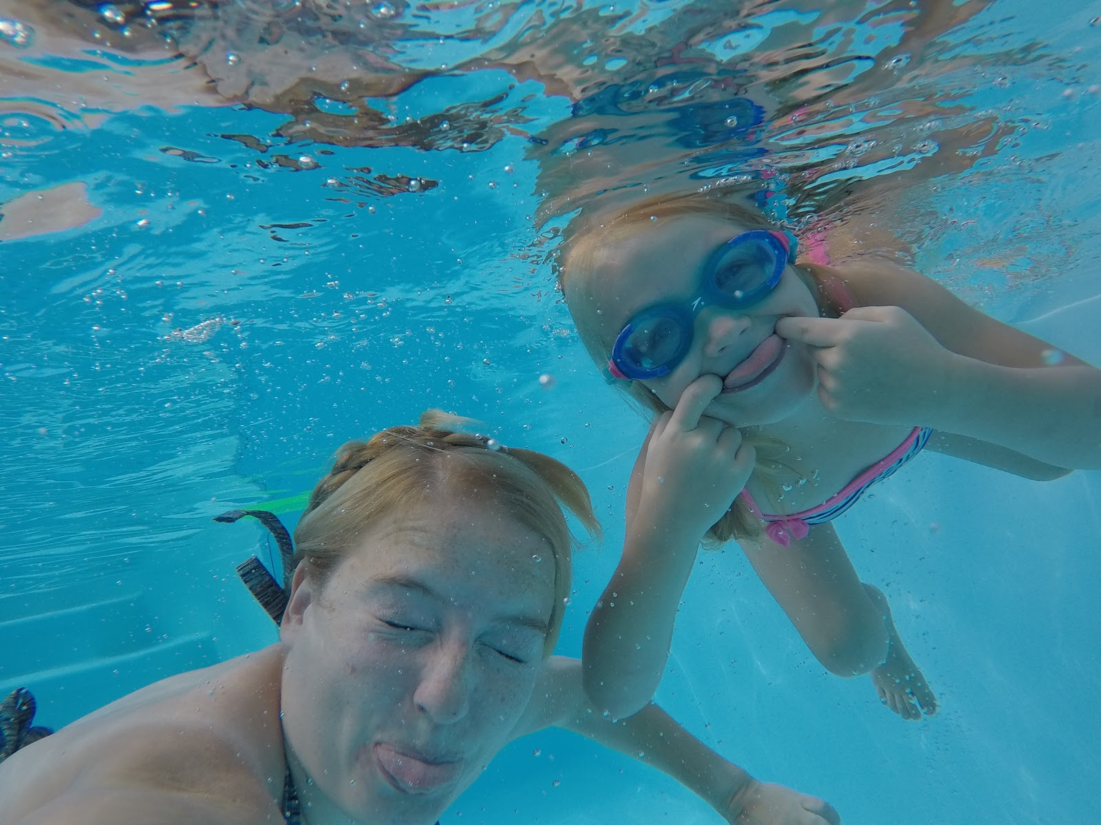Underwater photograph of my big girl and me pulling faces in a swimming pool