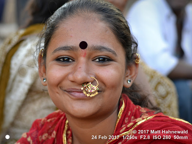 matt hahnewald photography; facing the world; face; bindi; eyes; laughing eyes; nose; nose piercing; nose jewelry; mouth; dimples; facial expression; eye contact; bareheaded; consent; empathy; emotion; fun; traveling; traditional; cultural; hinduism; mela; shivratri mela; bhavnath; junagadh; gujarat; western india; asian; indian; gujarati; one person; female; beauty; adult; young; woman; picture; photo; face perception; physiognomy; educational; nikon d3100; nikkor af-s 50mm f/1.8g; prime lens; 50mm lens; 4x3; horizontal; street; portrait; closeup; head shot; seven-eighths view; outdoors; color; posing; authentic; smiling; laughing; beautiful; fabulous; attractive; exotic; happy; cheerful; joyous; captivating; charming