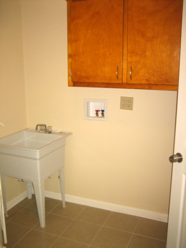 Our laundry room cabinets before their budget-friendly makeover