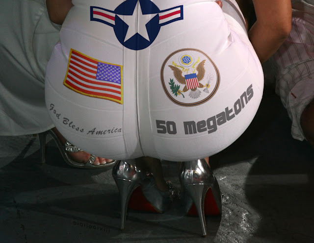 Close-up of Kim Kardashian squatting in white dress. The dress is covered in U.S. air-force insignia, including American flag and seal, and phrases: '50 Megatons' and 'God bless America'