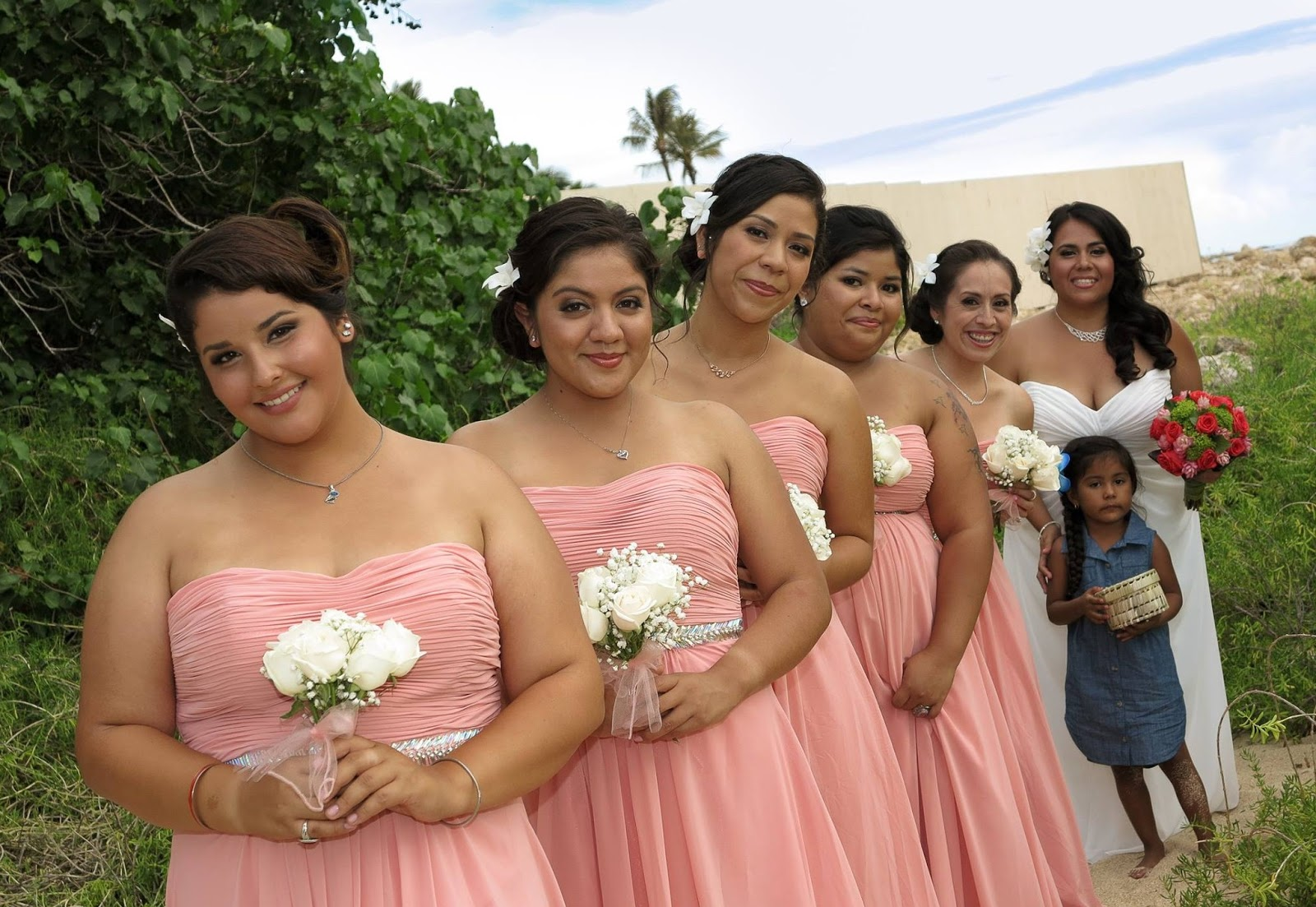 In A Beautiful Hawaii Beach Themed Wedding The Bridesmaids Are Stunning Floor Length Dresses Hues Of Pink And White With Small Bouquet