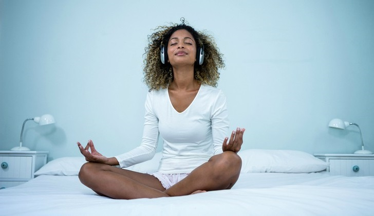 black woman meditating on bed with headphones