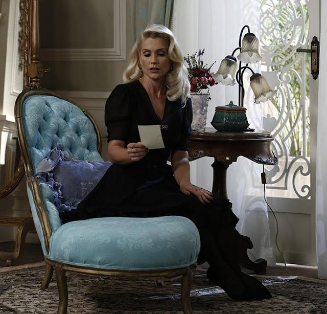 sandra sentada em uma poltrona lendo um bilhete com um vestido preto