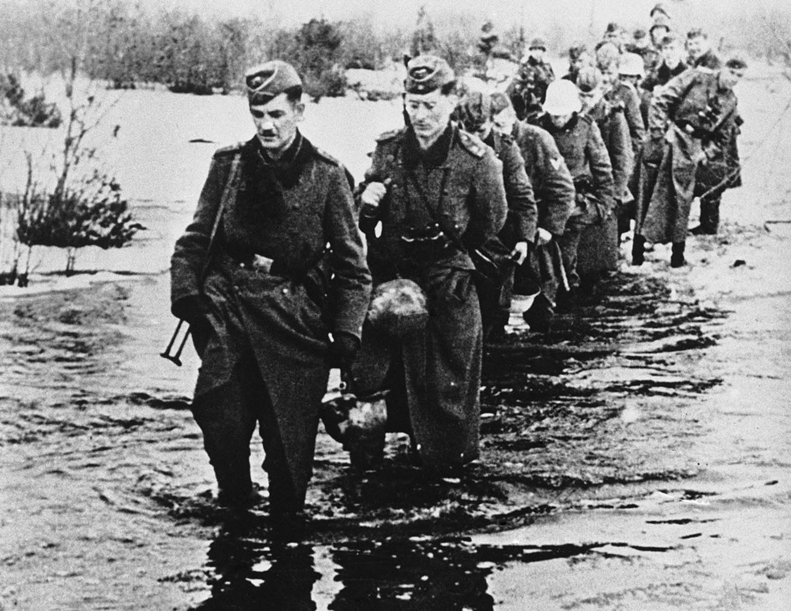 he appalling conditions ruling on the Russian front following the thaw when the winter snows melted and resulted in widespread floods on May 23, 1942. German soldiers wade through icy water which is knee deep, somewhere in Russia.