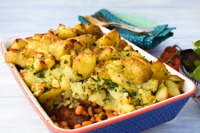 Cowboy Beans with Herby Crushed New Potatoes in a blue baking dish
