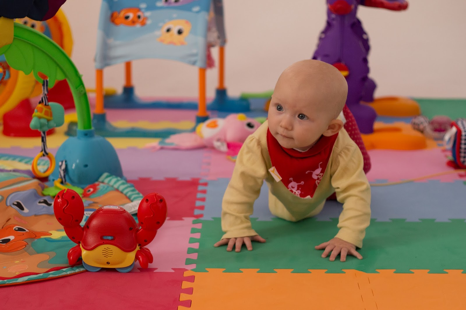 A baby crawling surrounded by Little Tikes toys on brightly coloured mats