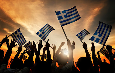 sunset with multiple people holding greece flags