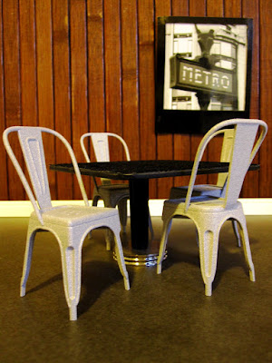 Corner of a modern one-twelfth scale miniature cafe with french cafe chairs and a black and white photo of a metro station entry on the wood-panelled walls.