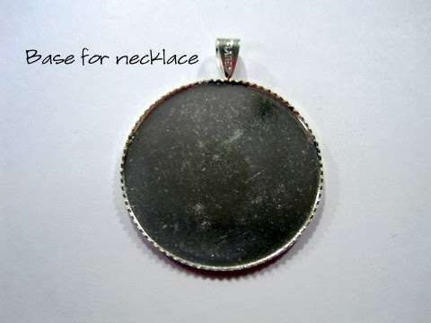 Silver coloured cabochon ready to be finished into a cross stitch necklace