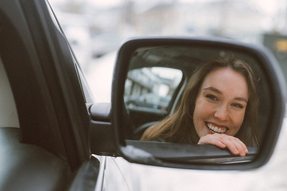 woman smiling in car mirror's reflection
