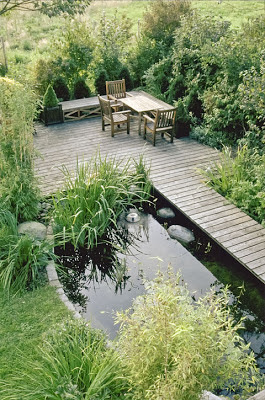 Sitzplatz am Wasser - ein Steg führt über den Teich zum Esszimmer im Freien