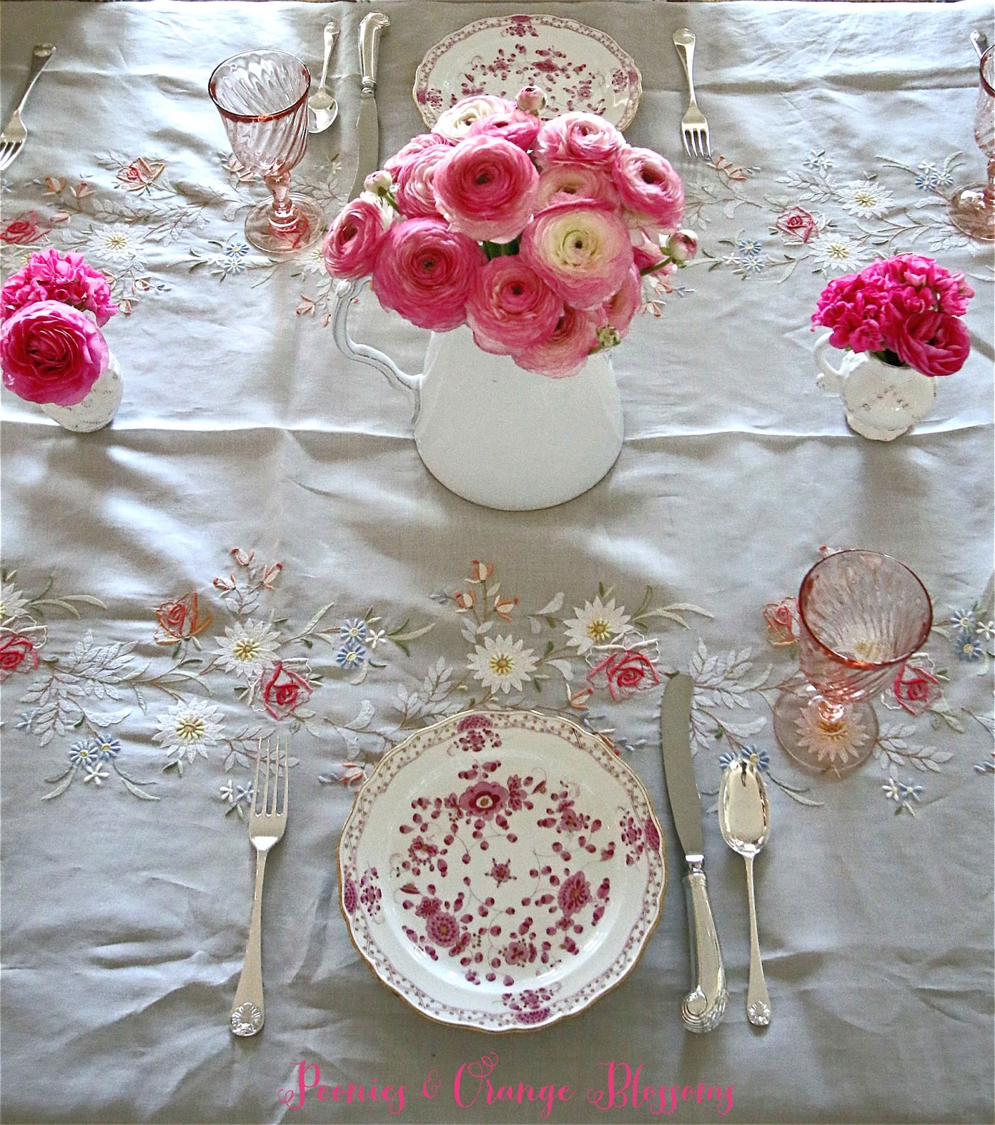 Spring French table setting with Madeira table cloth, Meissen plates, pink ranunculus, and vintage French goblets.