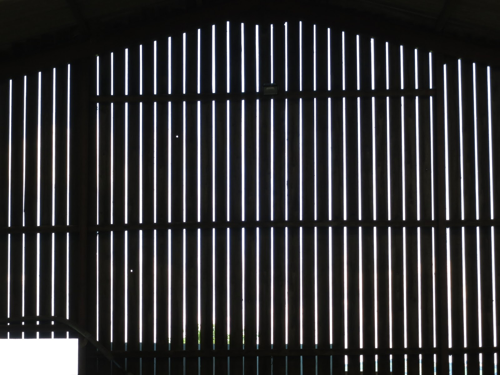 The area below the roof in the same barn. Dramatic slats made black in the glare of outside light
