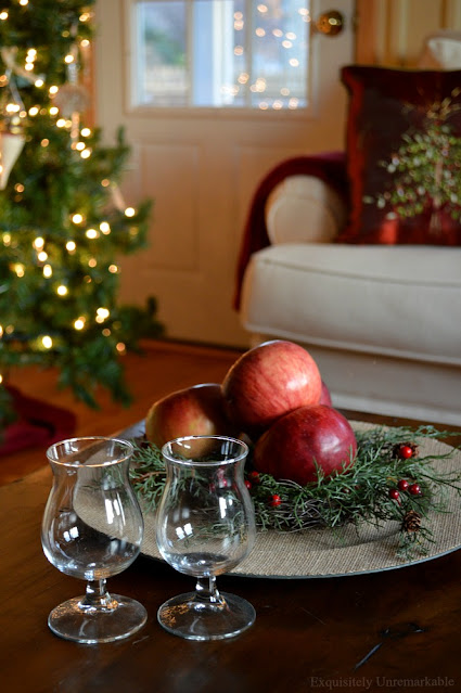 Rustic Christmas with tree lit in background and apples and brandy glasses on table