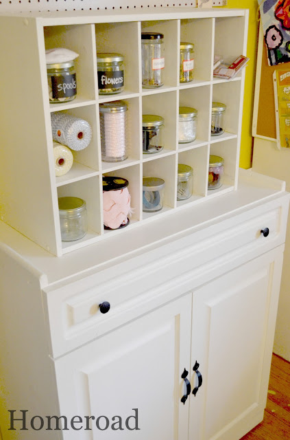 White cubbie shelf on top of white wooden cabinet