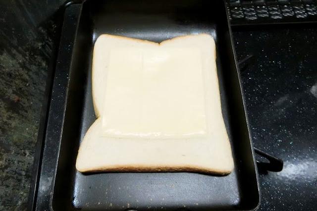 フライパンを熱し、バターを塗った面を下にして食パンを置きチーズをのせる