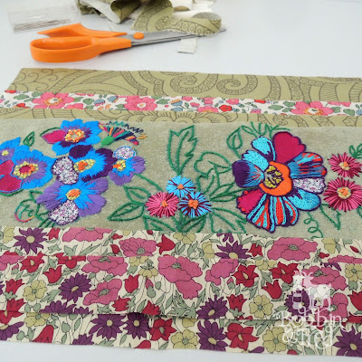 Hand stitch with floral fabric pattern in bright purple, blue, pink, orange and green