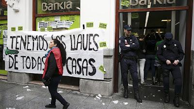 Una activista anti-desalojos pasa ante una pancarta mientras que unos policías bloquean la entrada de una sucursal bancaria de Bankia durante una protesta contra los desalojos en Madrid, España, el 11 de febrero de 2016.Andrea ComasReuters