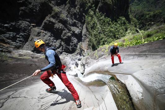 Hommes escaladent une cascade à la Réunion.