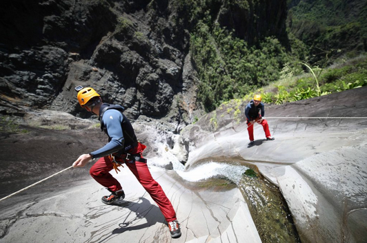 Hommes escaladent une cascade