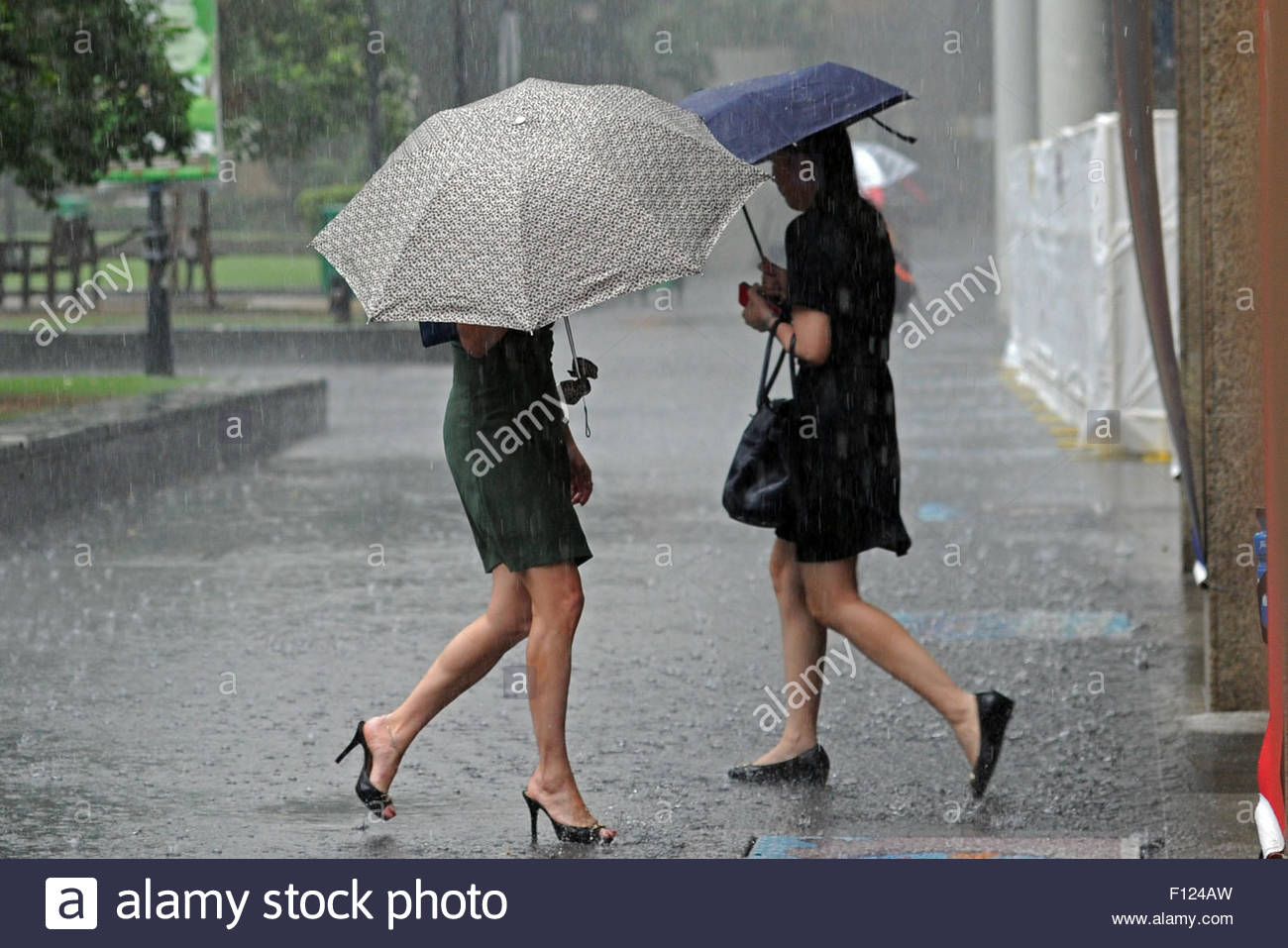 Women walk in the rain in Singapore's financial district Raffles Place on 25 August 2015.