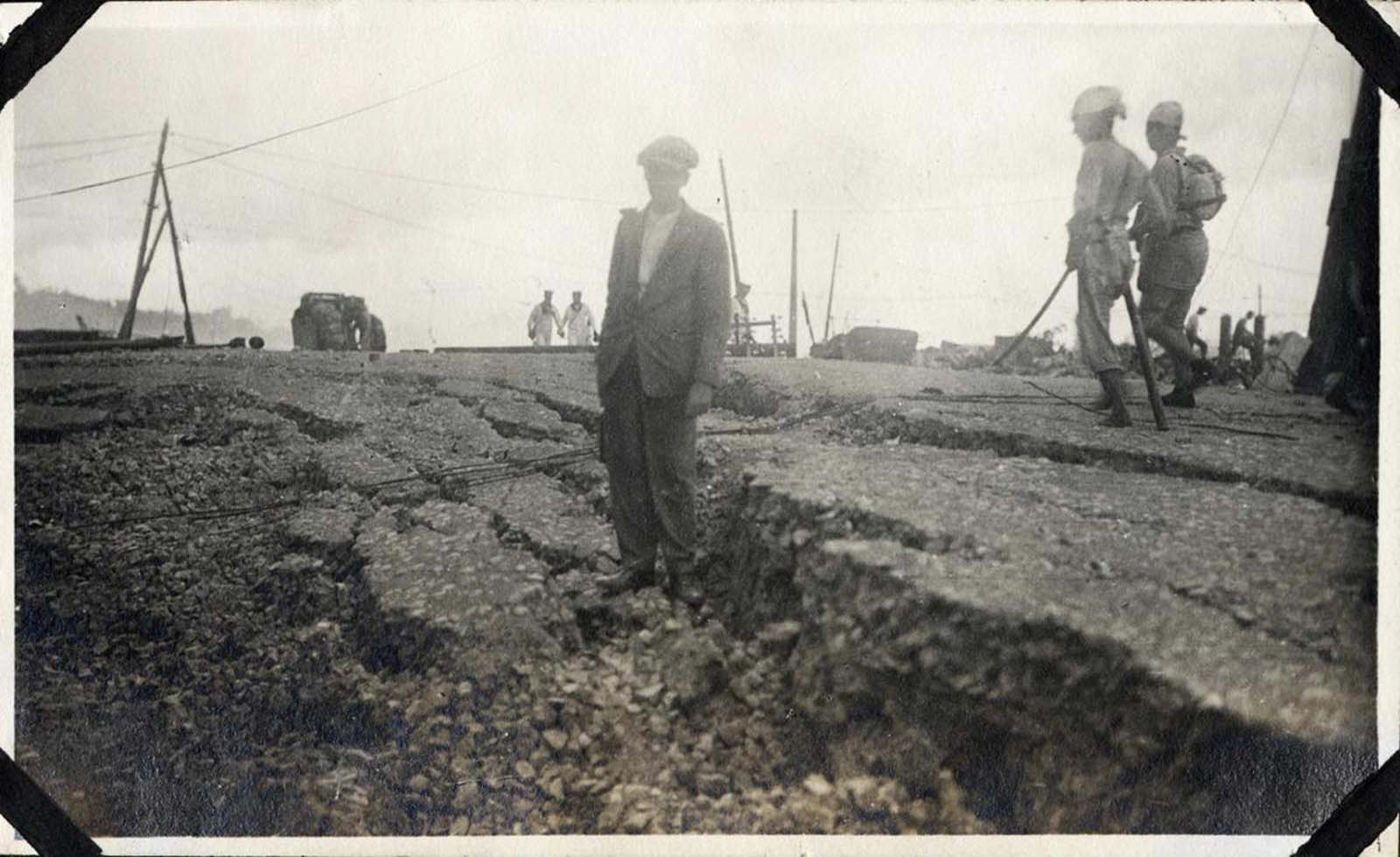 A man stands atop a fissured road.