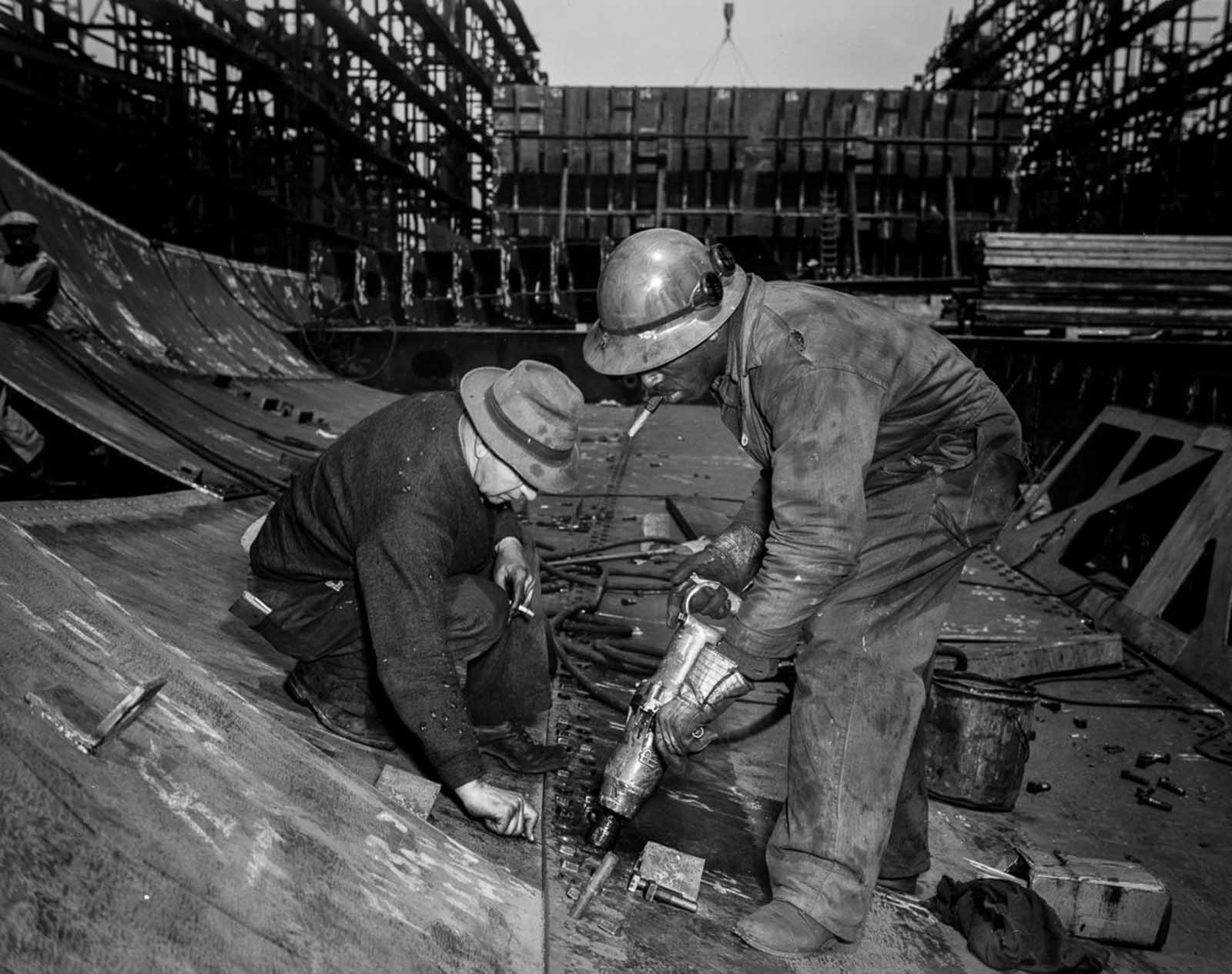 Workers tighten bolts with a pneumatic wrench in the belly of the Frederick Douglass.