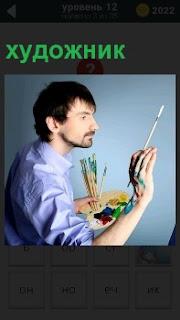 Мужчина на холсте используя кисточки в руках пишет картину с необычным выражением лица
