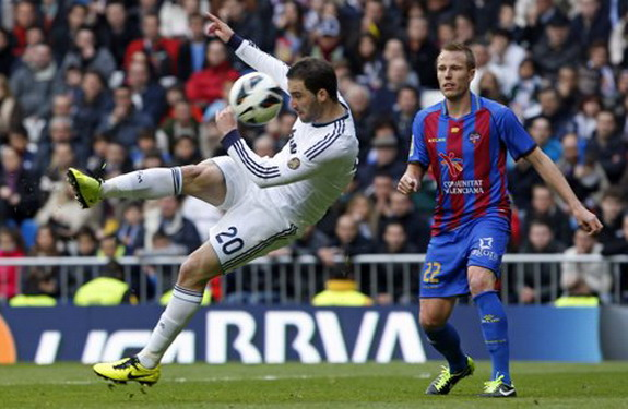 Real Madrid forward Gonzalo Higuaín shoots an acrobatic volley to score a goal against Levante
