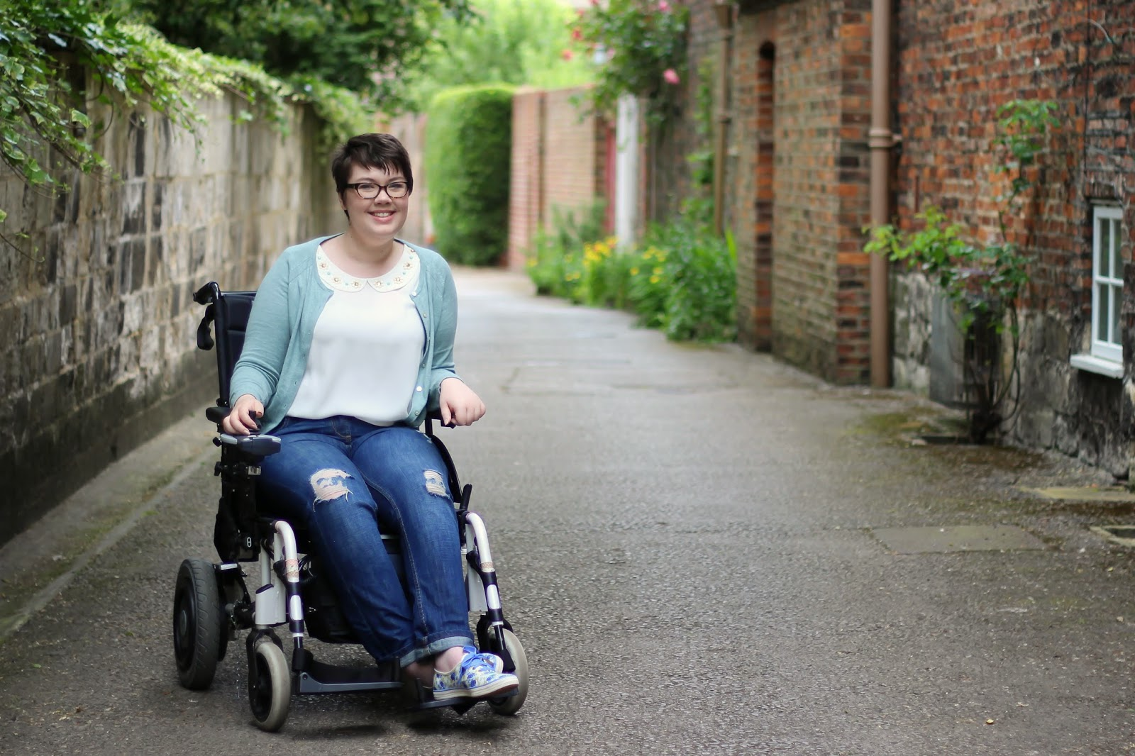 Wheelchair user wearing next jeans and taylor swift keds.