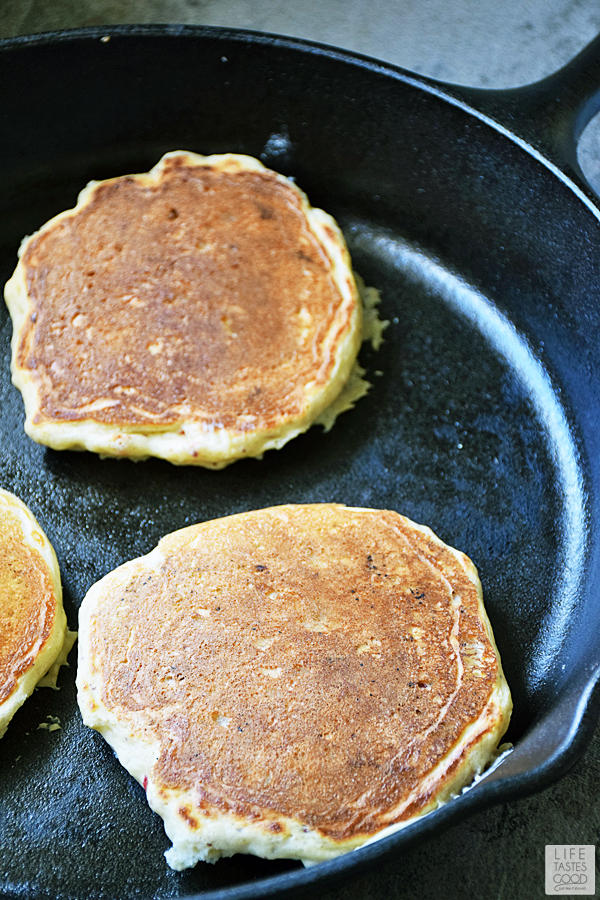 Strawberry Pancakes cooking in a cast-iron skillet