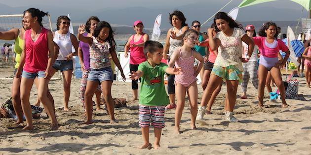 Niño y grupo bailando en la playa