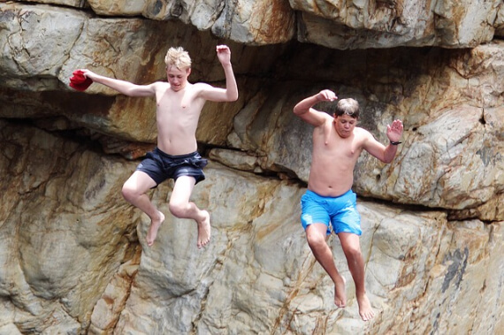 Two boys jumping off cliff in swimsuits #vanlife