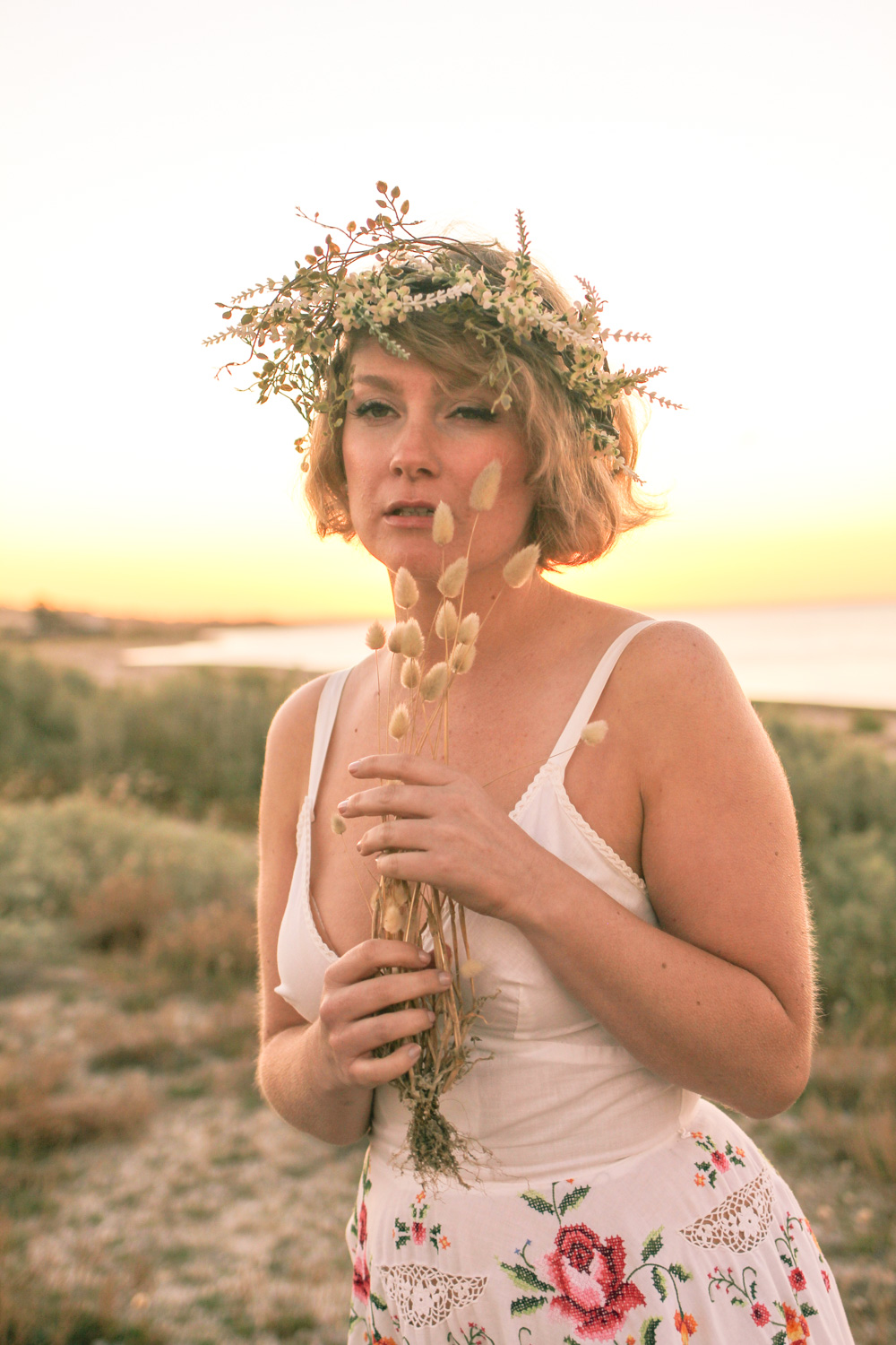@findingfemme in a twiggy flower crown and cross stitched dress at the beach.