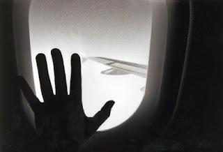 [una persona ha messo la mano sul finestrino dell'aereo]