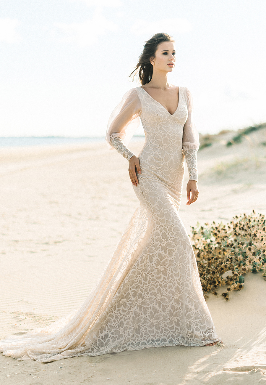 The stunning lace low back wedding dress has sheer long sleeves and a floral lace pattern. This affordable wedding dress is just one of many wedding dresses from She Wore Flowers