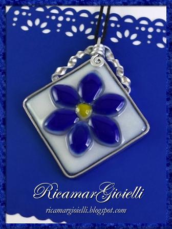 Ciondolo con fiore blu e sfondo bianco realizzato in vetrofusione e ingabbiato in wire