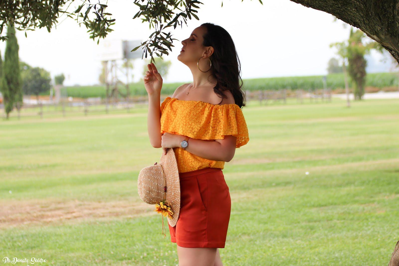 Top giallo e pantaloncino arancio look che risalta l'abbronzatura