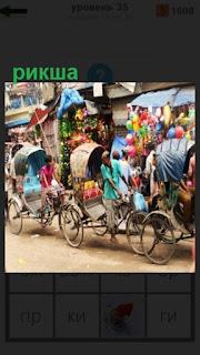 по улице едет рикша и перевозит людей