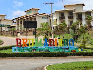 entrada da cidade de brumadinho com casas ao fundo e na frente letras coloridas formando o nome da cidade