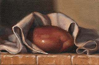 Oil painting of a Désirée potato in the folds of a loosely arranged tea towel.