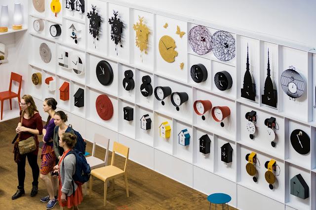 Foto que mostra um a parede cheias de relógios