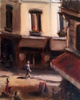 Oil painting of a male figure walking in a narrow and partially sunlit street surrounded by shops.