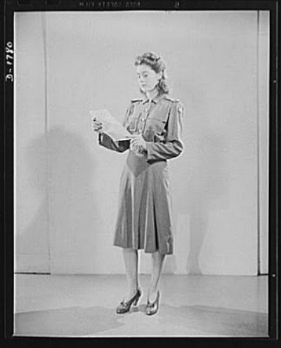 Woman in Office of Indorr Staff Civil Defense Uniform reading a paper