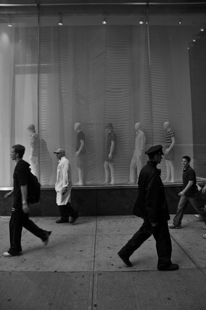 People walking past department store window
