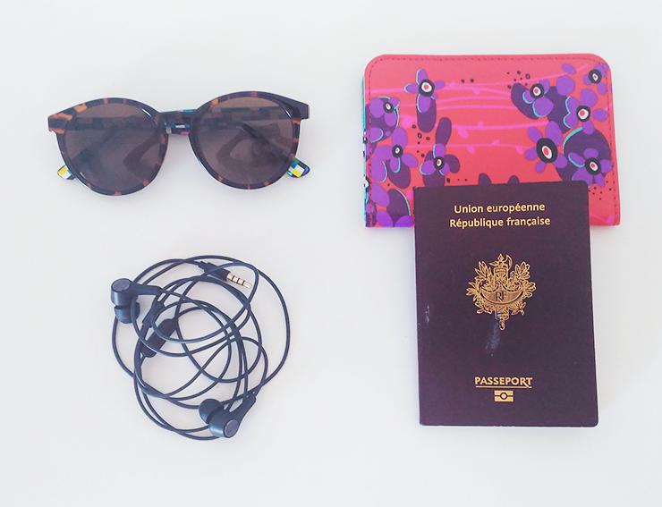 Lunettes, ecouteurs audio, passeport, pochette pylone, l'attirail pour partir vivre à l'étranger