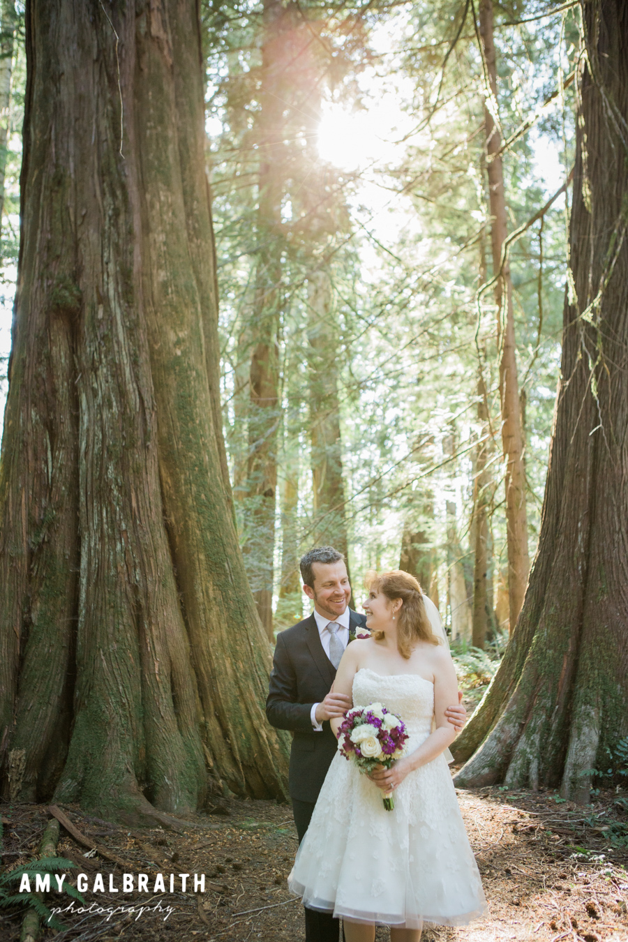 bride and groom standing next to giant tree in rainforest